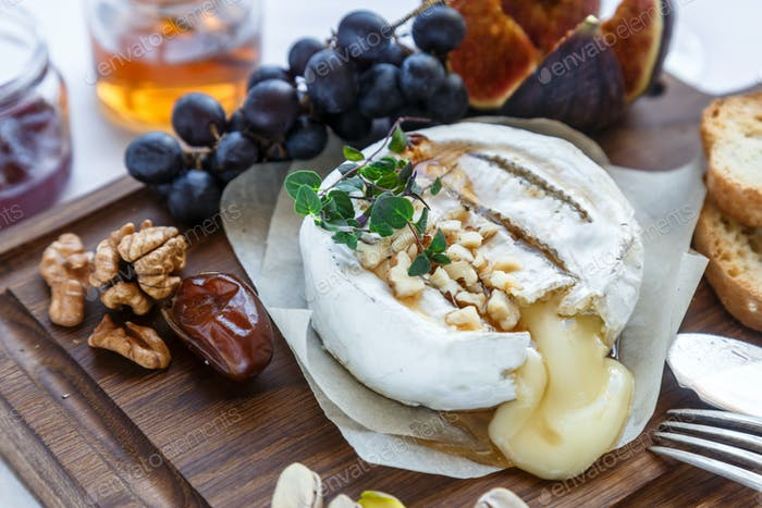 Baked camembert cheese with figs, honey, grapes and nuts. Top view