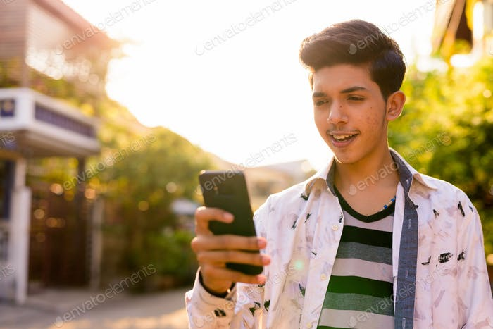 Young handsome Indian teenage boy in the streets outdoors