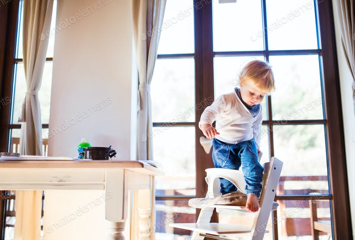 Toddler boy in a dangerous at home, climbing into highchair.