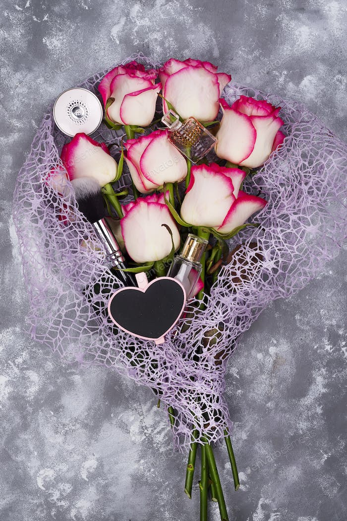Bouquet of beautiful roses with cosmetics on gray concrete
