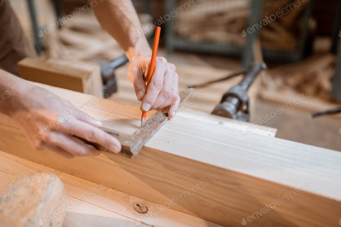 Carpenter working with a wood indoors
