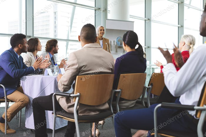 Group of business people applauding in a business seminar in modern office building