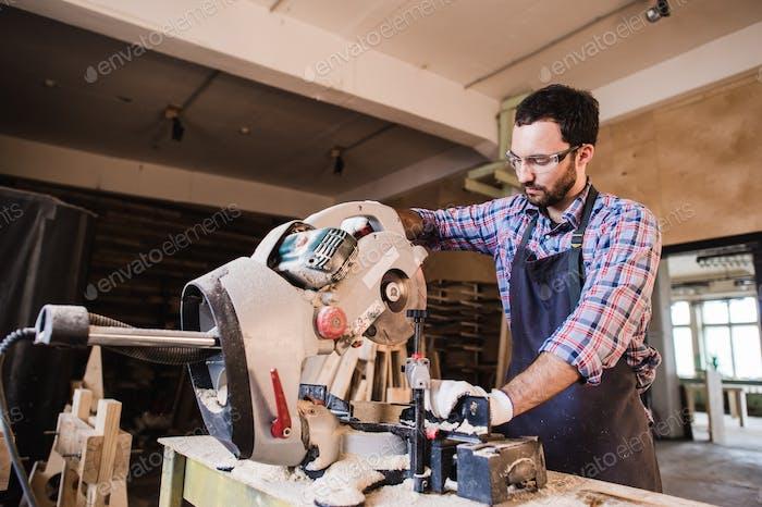 Carpenter Using Circular Saw for wood at his workshop