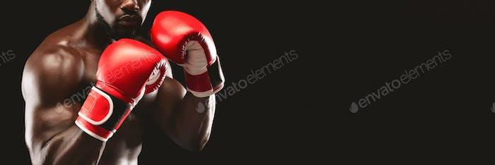 Cropped image of black boxer showing defending pose