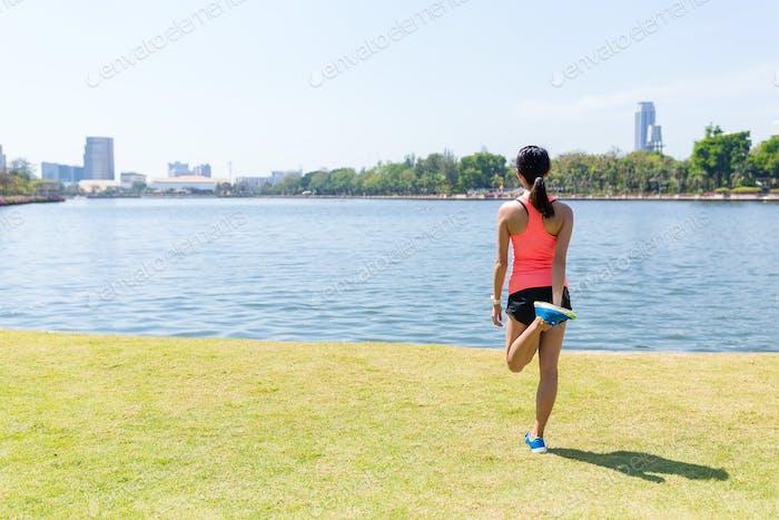 Frau streckt sich auf ihren Beinen im Stadtpark