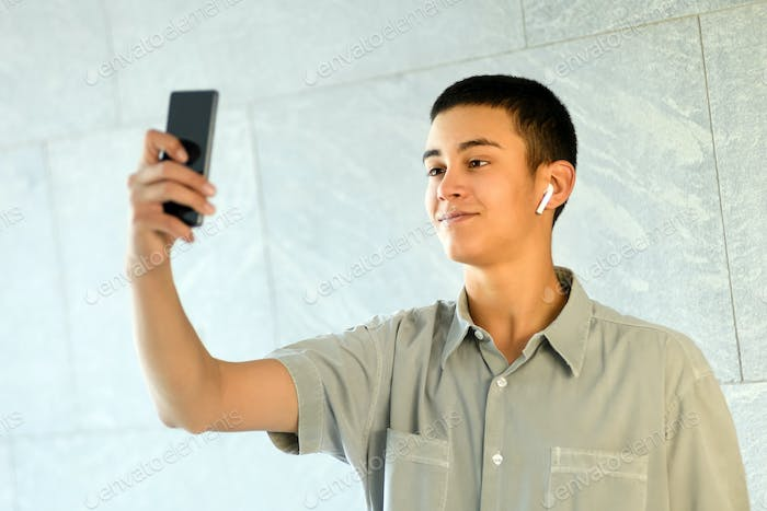 Young man wearing an earbud taking a selfie