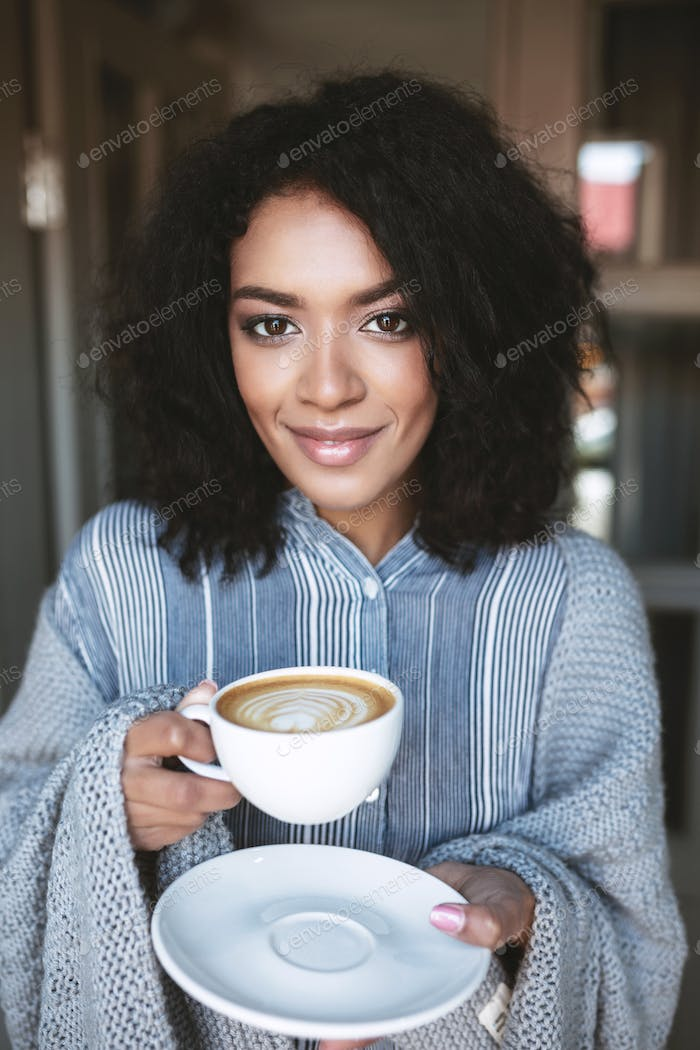 Young smiling African American girl drinking cappuccino and looking in camera