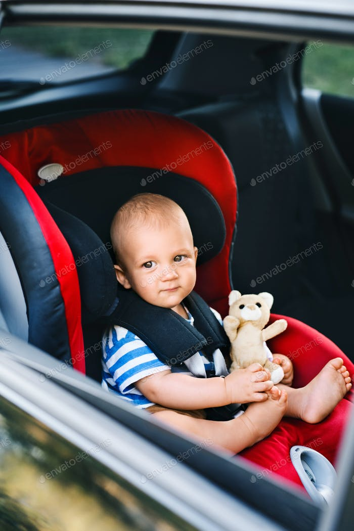 Little baby boy sitting in the car seat in the car.