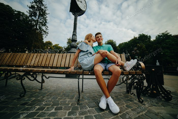 guy and girl sitting on a bench