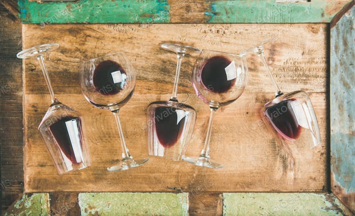 Red wine in glasses over rustic wooden tray background
