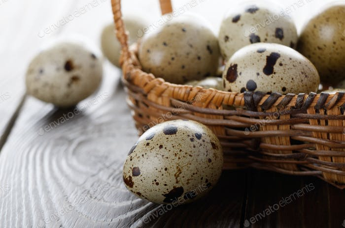 Fresh organic quail eggs in small wicker basket on rustic kitche
