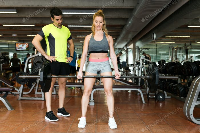 Sporty young couple doing muscular exercise in gym.