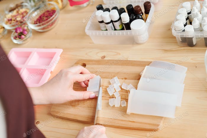 Hands of woman chopping white hard soap mass on wooden board by table