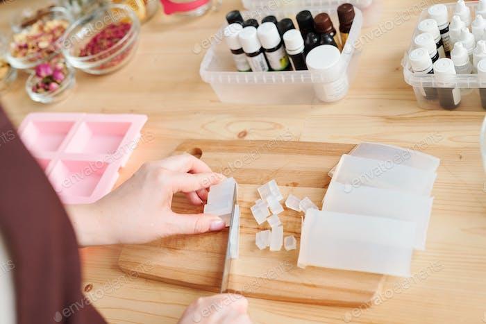 Hände der Frau hacken weiße harte Seifenmasse auf Holzbrett für Tisch