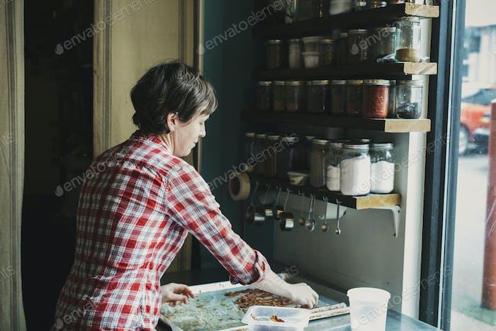 Eine Frau mit einem Tablett gekochtem Speck in einer Coffee-Shop-Küche.