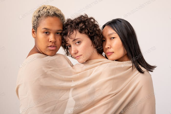 Group of young intercultural females wrapped into white linen looking at you