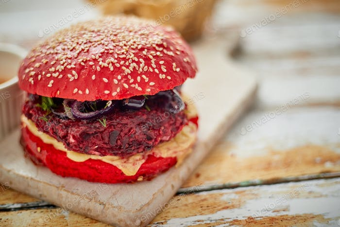 Homemade vegetable beetroot burgers. Red colored sesame bun. Served with goat cheese, feta