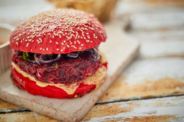 Hausgemachte Burger aus Gemüse mit Rote Beete. Rot gefärbtes Sesambrötchen. Serviert mit Ziegenkäse, Feta
