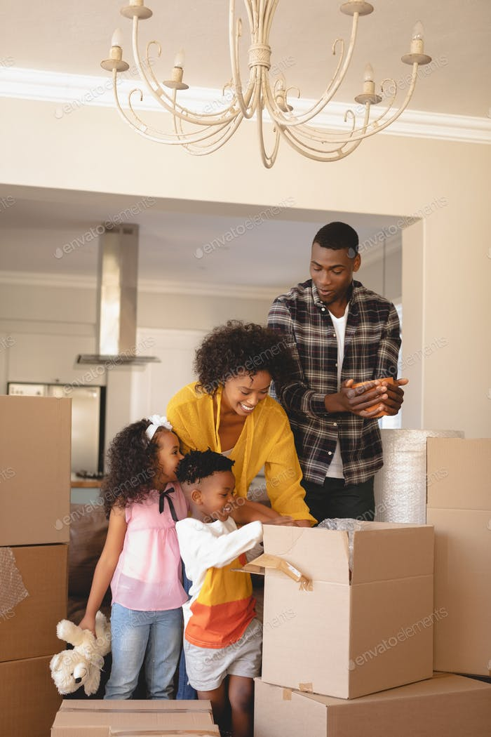 Happy African American parents with their children packing their belongings in living room at home