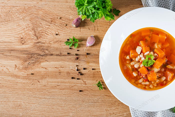 Tomato chicken soup with pumpkin and white beans in white bowl. Top view