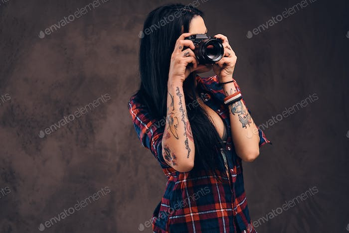 Sexy tattooed hipster girl wearing a red unbuttoned checkered shirt and shorts