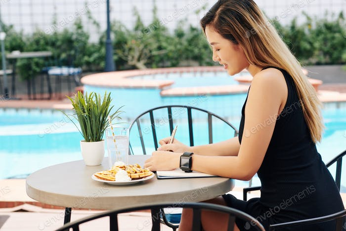 Woman eating breakfast and filling journal