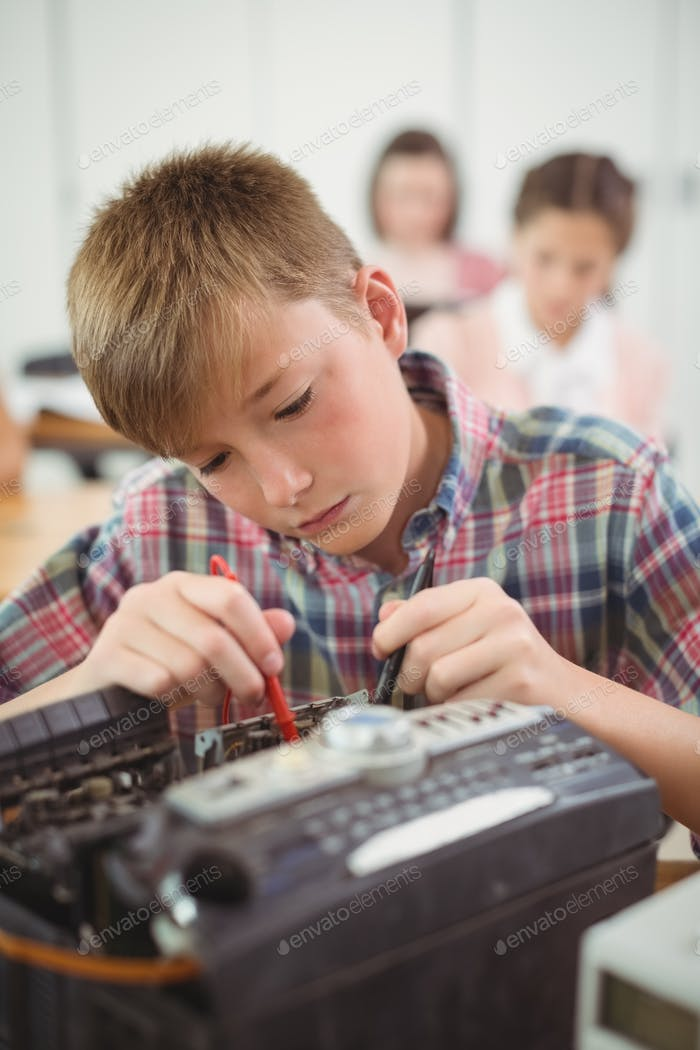 Schoolboy repairing a printer in the classroom