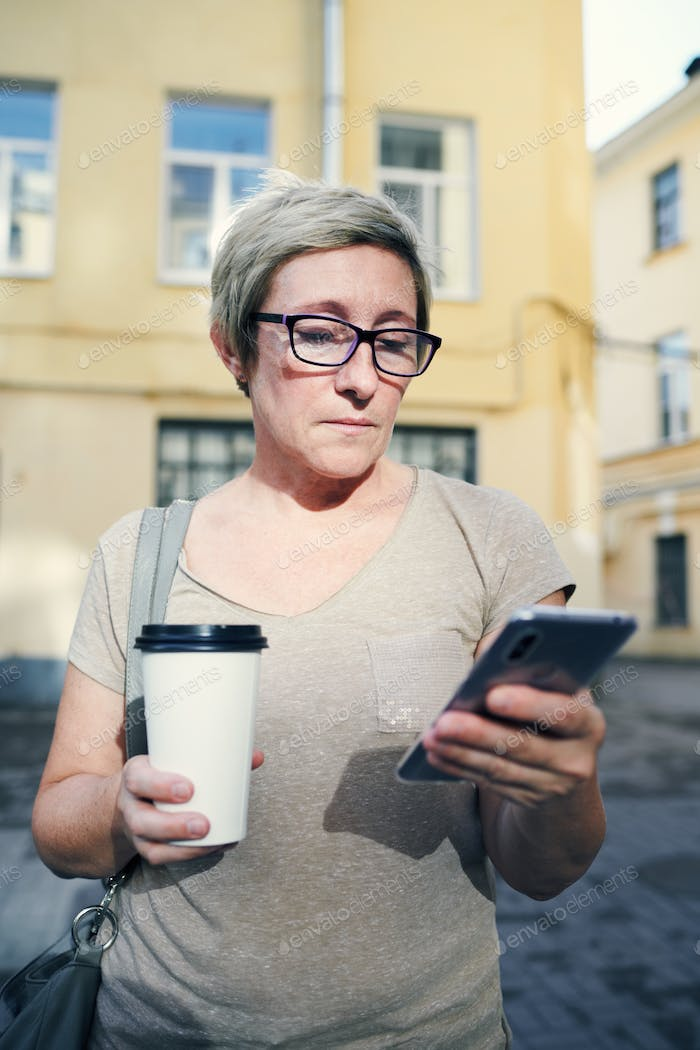 Senior woman with drink using smartphone