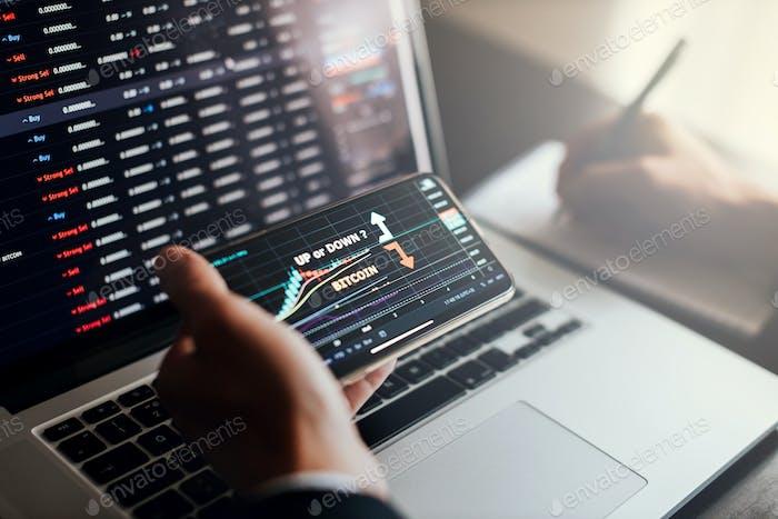 Börsenmakler mit Telefon und Laptop für Gewinngewinn-Analyse Arbeitsplatz