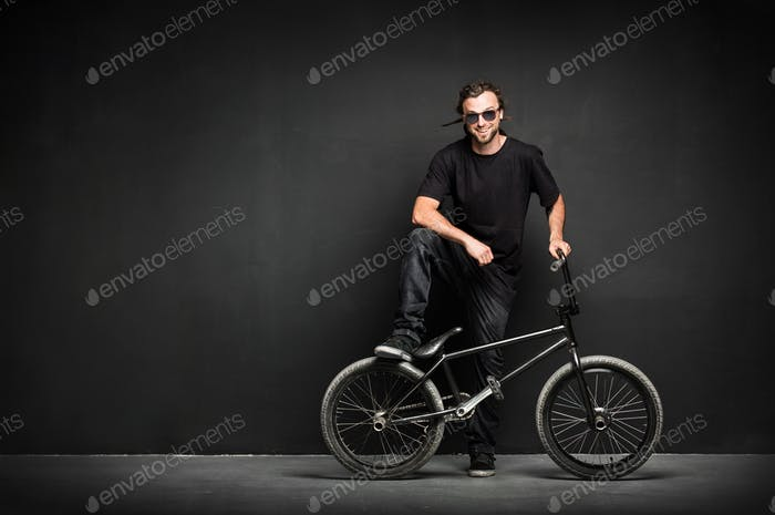 Smiling man with dreadlocks standing with his BMX