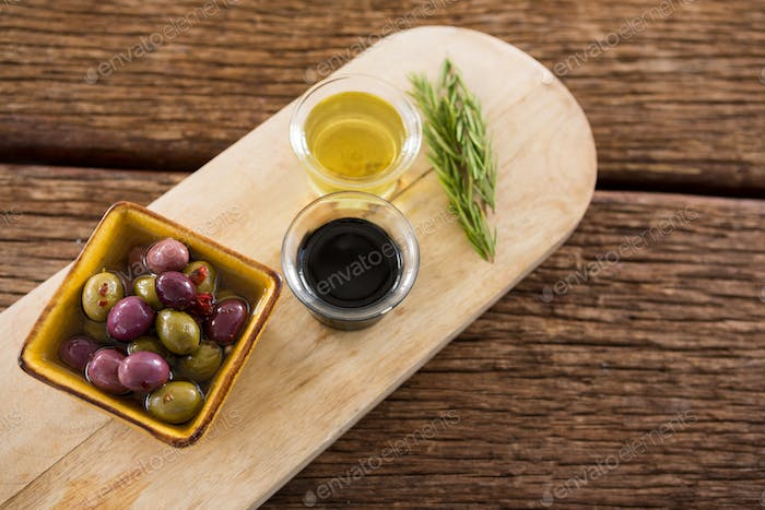 Marinated olive, rosemary with olive oil and balsamic vinegar on table