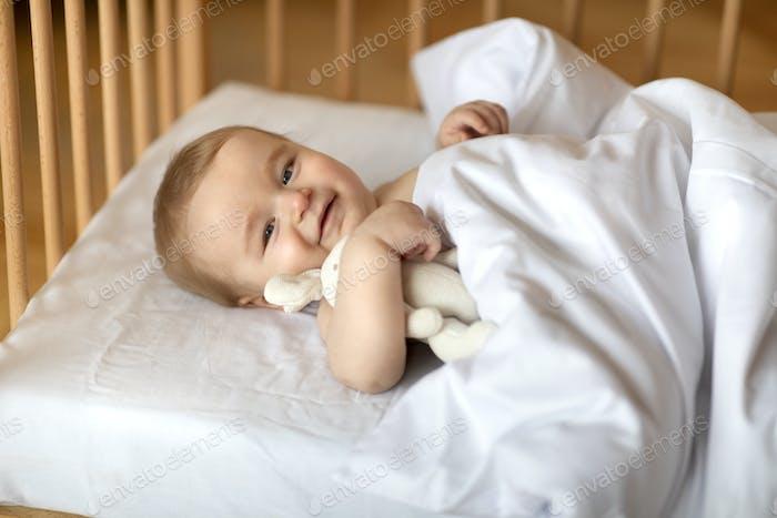 Smiling baby under blanket in wooden crib