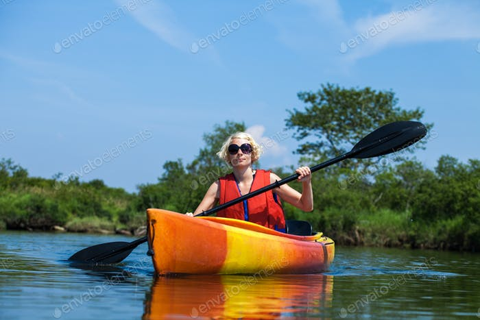 Woman With Safety Vest Kayaking Alone on a Calm River