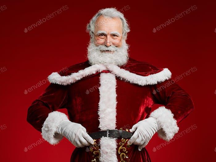 Weihnachtsmann posiert gegen Rot