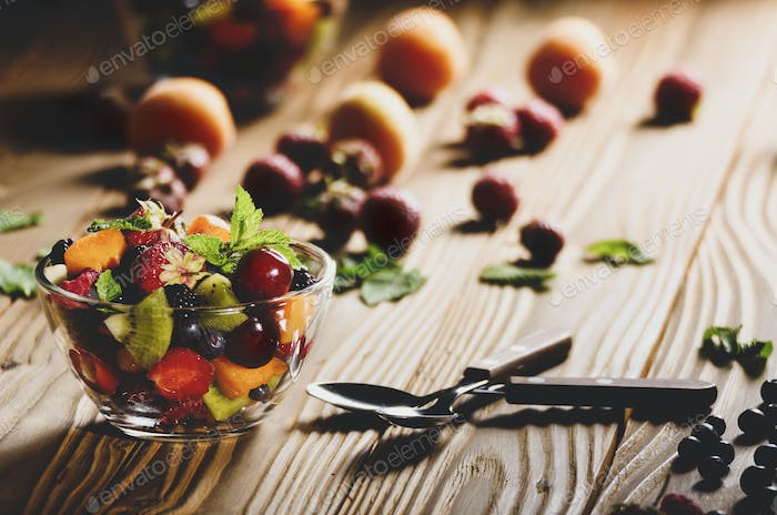 Assorted fruits in glass bowl on kitchen wooden table with spoon