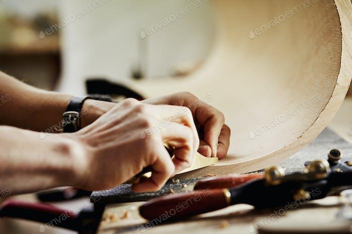 Un hombre en un taller de muebles trabajando en un pedazo de madera curvada.