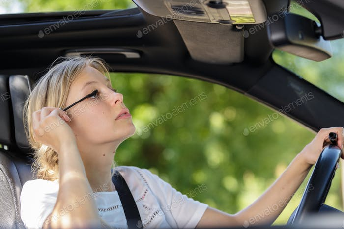 young woman putting her mascara in the car