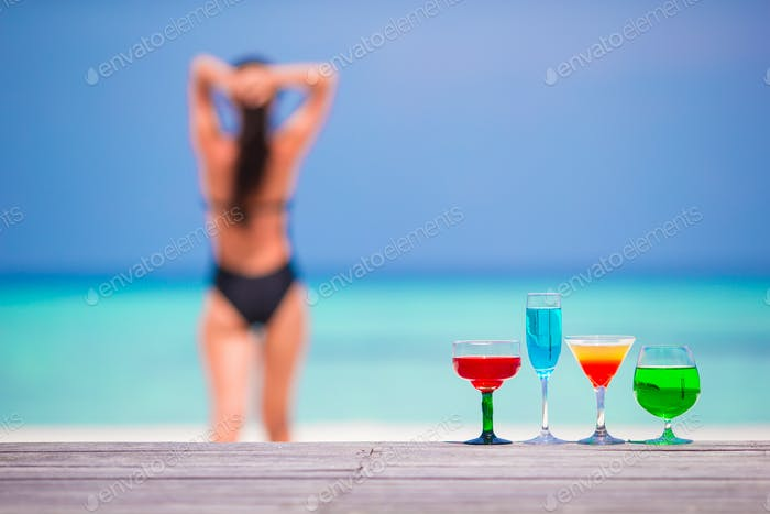 Exotic tasty cocktails in outdoor cafe background turquoise sea and girl