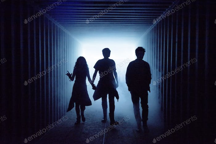 Silhouette of people walking in a dark subway tunnel to the light