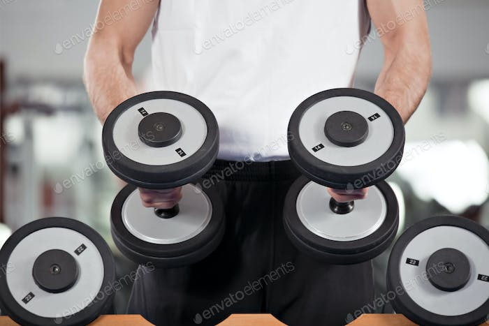 Man Lifting Weights In Fitness Gym