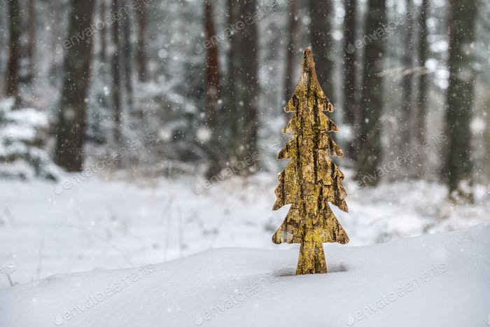 Wooden shaped pine tree in the snow in forest. Christmas tree