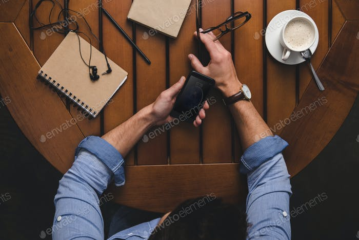 overhead view of man using iphone at wooden table with coffee and notepads