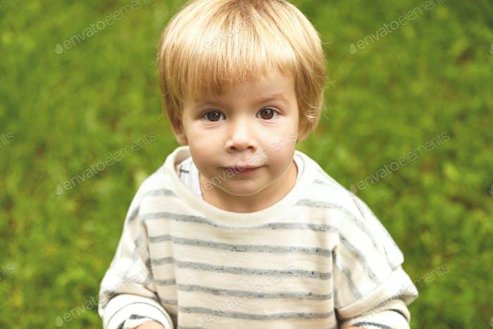 Charming close-up innocent portrait of little innocent kid. Calm Caucasian boy with blond hair, roun