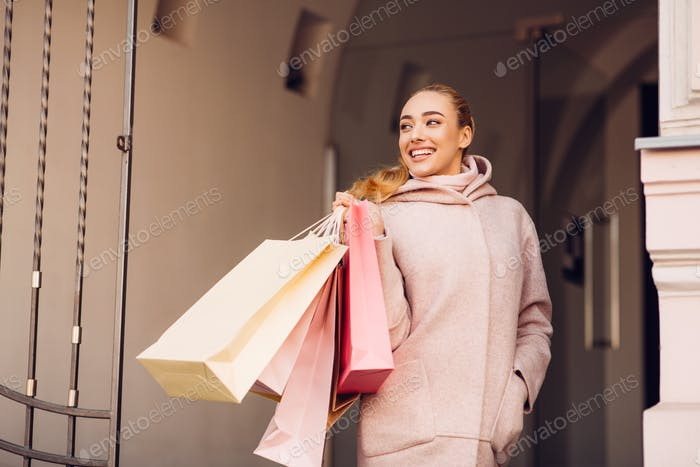 Shopaholic woman with shopping bags, walking in the city