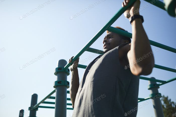 Muscular black man performing pull-up exercise