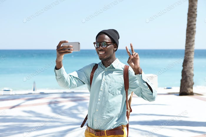 Handsome cheerful young black male tourist with backpack holding cell phone, making peace gesture an