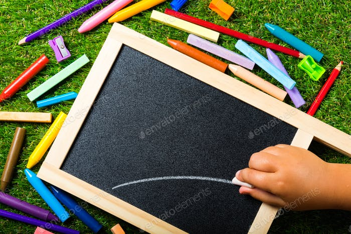 Top view of mini blackboard and colors on plastic grass background. Concept back to school