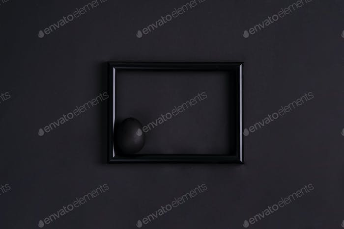Black easter egg by paintbrash in black color on the black photo frame and black background