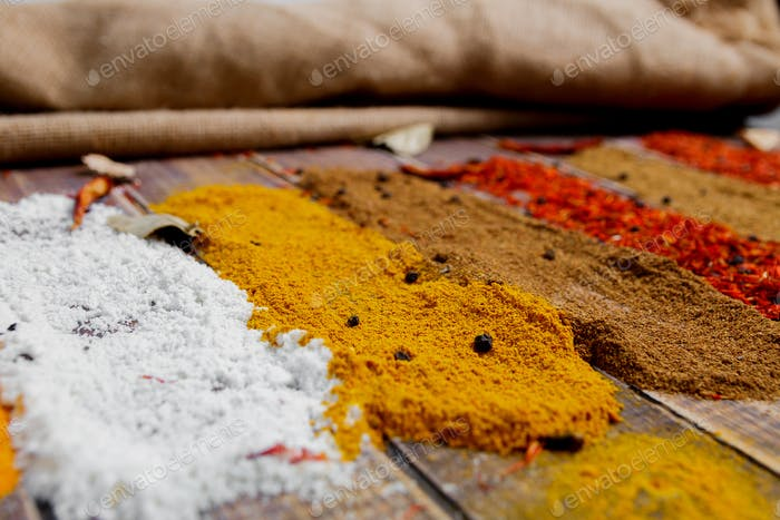 Colourful spices on the table. Various Spices in on wooden background. Spices background.