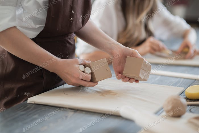 White clay preparation for work. Cutting layers of clay pieces for sculpting in the workshop of a